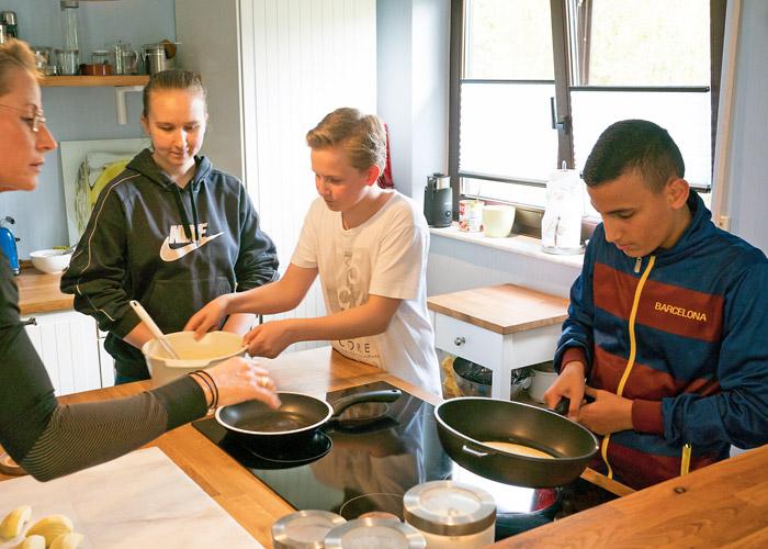 Kinder lernen kochen und essen.